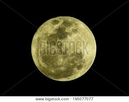 Close up of the yellow full moon texture in the night time. Full moon isolated on black background.