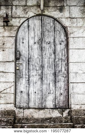 Old wooden door vintageThere is a bell on the wall.