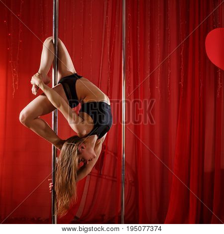Sexy pole dancer performs on a pylon. She hangs on the pylon upside down. Flexibility plasticity and strength.