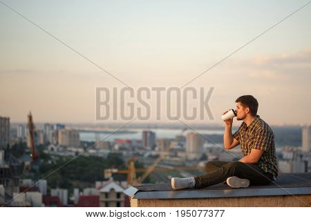 A man drinks coffee early in the morning on the roof. He looks away and thinks. In the background the city landscape