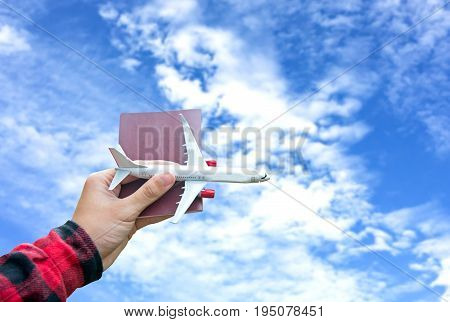 Tourist holding airplane flight travel and passport traveller fly travelling citizenship air on blue sky background. Travel Concept.
