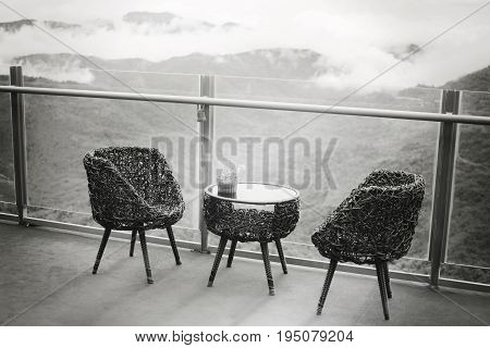 Rattan table and chairs set for relaxing and admiring misty valley views with selective focus. Black and White retro concept.