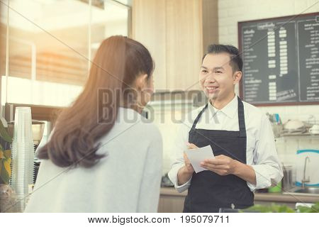 Asian barista man standing for taking order with attractive smiling at coffee shop. Man with owner business concept. 30-40 years old.