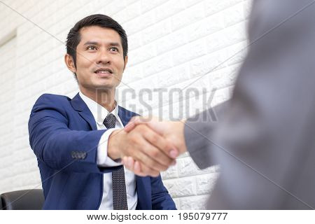 Young asian businesspeople shaking hands greeting each other Business people working with agreement concept.