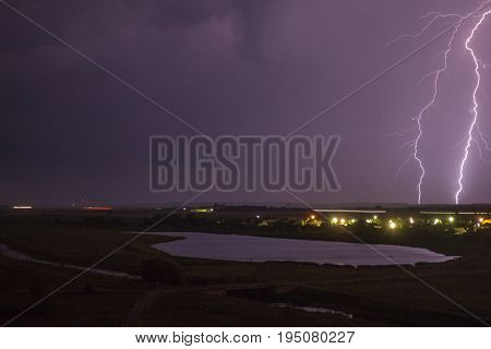 A lightning bolt in the dark sky above the countryside. Landscape