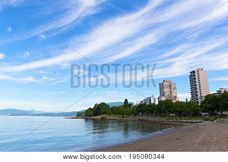 Vancouver urban landscape with a sandy sea beach and park British Columbia Canada. Summer in Vancouver with snow mountain peaks on horizon.