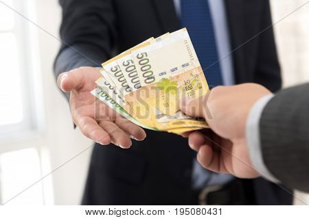 Businessman giving money South Korean won banknotes to his partner