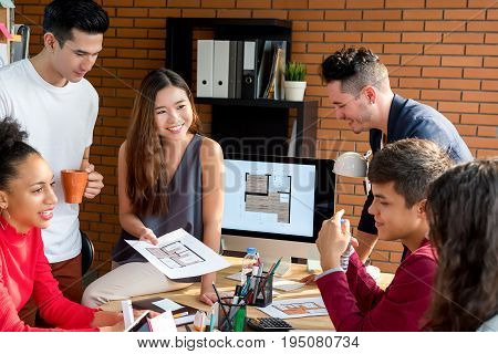 Casual Asian businesswoman sitting on the table presenting work to her multiethnic colleagues in the meeting