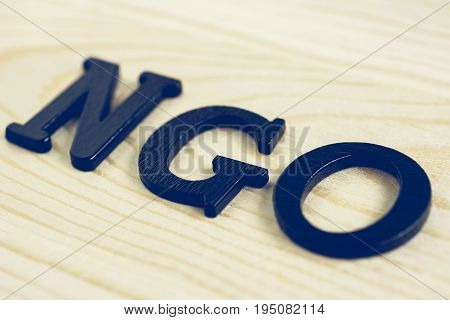 NGO letters on wood background - NGO stand for Non-Governmental Organization