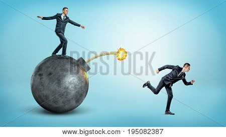 A businessman standing on a black round bomb with a lit fuse beside a man running away from it. Business competition. Drastic measures. Flee from trouble.