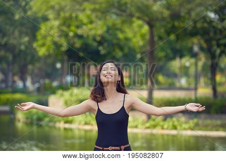 Waist-up portrait of beautiful Asian woman enjoying fresh air in picturesque green park while standing at lake with outstretched arms and closed eyes