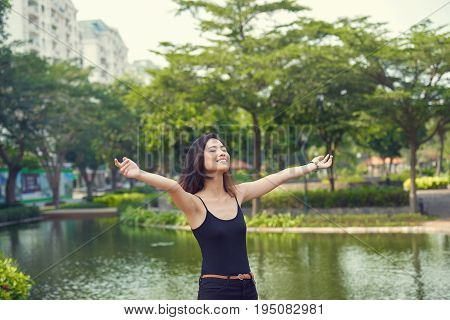 Attractive Vietnamese woman feeling unity with nature while standing at lake with outstretched arms and closed eyes, waist-up portrait