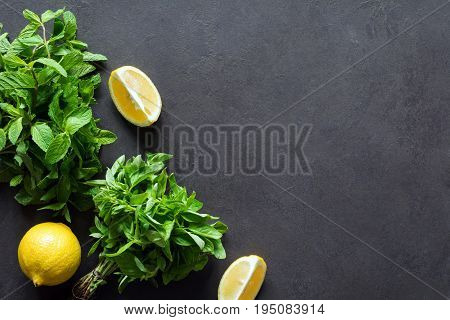 Fresh mint basil bunch and lemons on dark slate chalkboard background. Top view copy space. Ingredients for summer refreshing drink cocktail