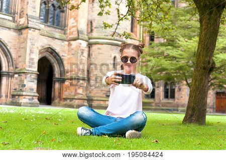 Young lady sitting on the grass and taking photography in Glasgow University garden. Summertime outdoors.