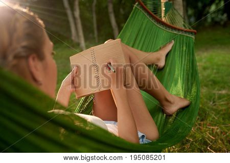 Over shoulder view of fair-haired young woman writing down ideas in notepad while lying in hammock and working on promising project, lens flare