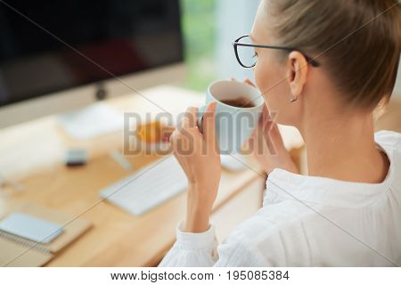 Unrecognizable manager in eyeglasses enjoying fragrant herbal tea while sitting at office desk, over shoulder view