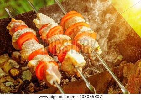 Pieces of pork with tomato slices being roasted on skewers over charcoal