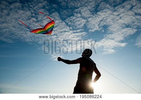 Silhouette of a young man holding a kite flying in beautiful blue sky with clouds at sunset