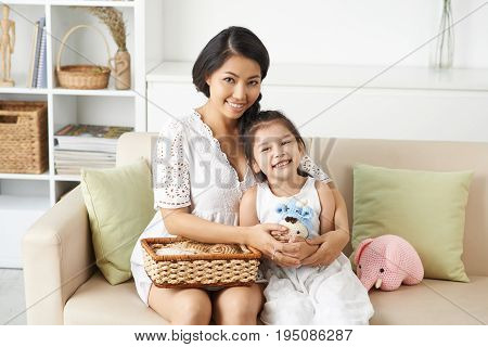 Beautiful Vietnamese woman and her little daughter knitting toys