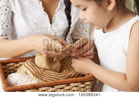 Close-up image of woman teaching her little daughter crocheting