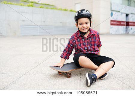 Multi-ethnic smiling boy in helmet sitting on skateboard