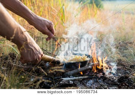 Cooking food in pan on camping fire. Hands hold frying pan and fork preparing simple tourist food in open fire outdoors in camping trip