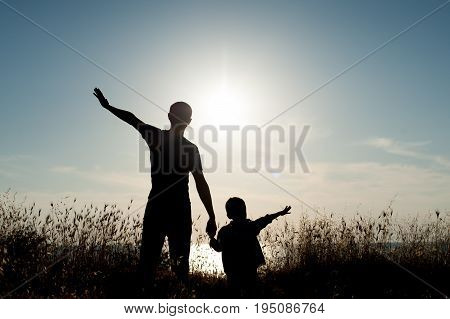 happy man and little kid among grass on sea sunset background