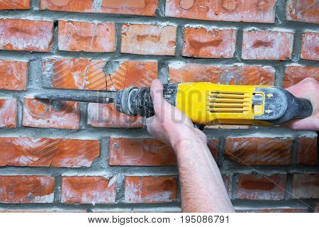 Builder with hammer drill concrete on a construction site