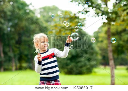 Little blonde cheerful girl playing with soap bubbles in the green summer park. Outoors.