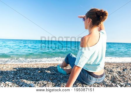 Young teenage fashionable girl looking over Mediterranean Sea view sitting on pebble coastline. Multicolored summertime outdoors horizontal image with blue sky background.