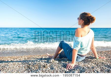 Young teenage fashionable girl contemplating Mediterranean Sea sitting on pebble coastline. Multicolored summertime outdoors horizontal image with blue sky background.