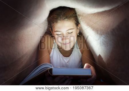 Young cheerful teenage girl hiding under blanket and reading book in the darkness. Key light coming from book. Indoors horizontal image.