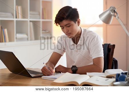 Portrait of Vietnamese student concentrated on essay