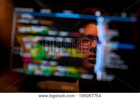 Asian software developer analyzing data on computer screen