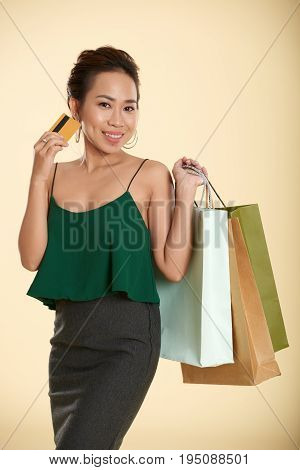 Portrait of attractive Vietnamese lady with credit card and shopping bags