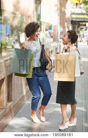 Pretty female shopaholics cracking jokes and laughing a lot