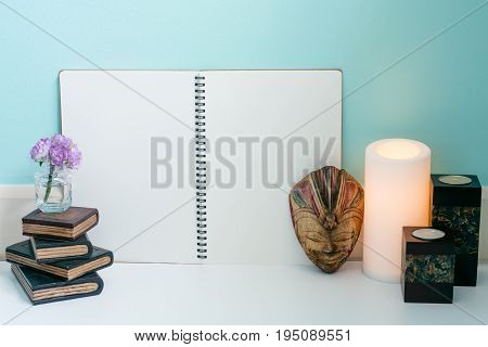 Wooden book flower wooden Bali mask warm light candle and classic candles with blank page notebook blue pastel wall background warm and relax feeling