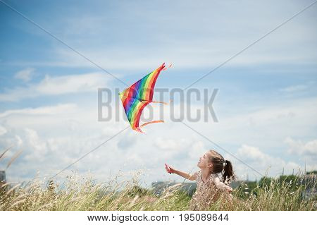cheerful smiling little caucasian girl holding flying kite in field on blue cloudy sky background on sunny summer day