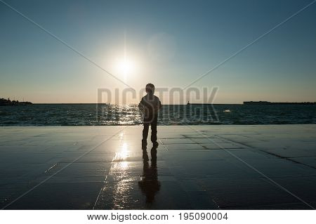 one little boy watching the sea against the sunset
