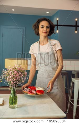 Portrait of a smiling young waitress in apron serving donuts on a tray in a caffeteria