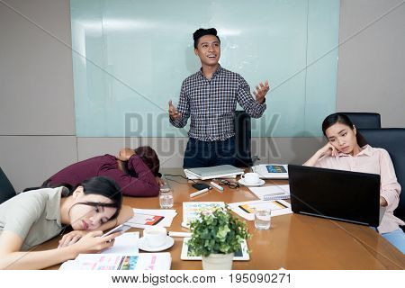 Enthusiastic Vietnamese businessman telling his idea to bored coworkers