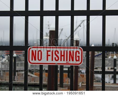 Red and white sign stating No Fishing posted on a black wrought iron fence