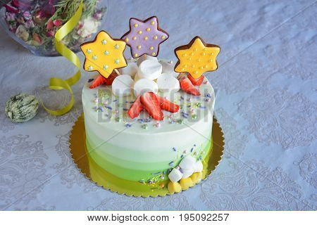 Homemade white and green ombre cake with strawberries marshmallows and gingerbread stars on white background