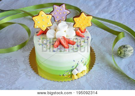 Beautiful white and green ombre cake with strawberries marshmallows and gingerbread stars