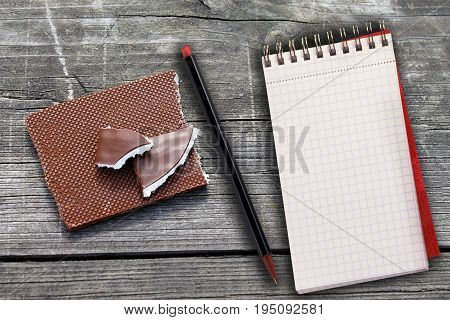 Broken chocolate on a wooden background. In the photo there is a notepad for your text.