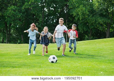 Cute Happy Multiethnic Kids Playing Soccer With Ball In Park
