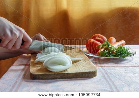 Hands chopping onions on wooden board with tomatoes, carrots and verdure on the table