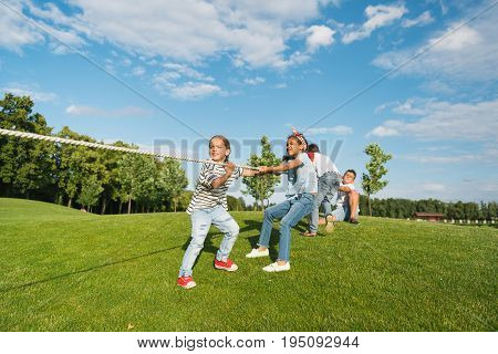 Multiethnic group of kids playing tug of war on green grass in park