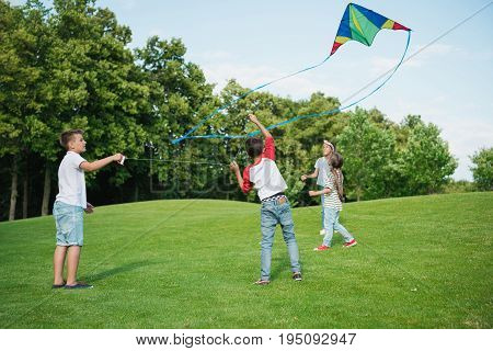 Cheerful multiethnic kids playing with kite on green lawn in park