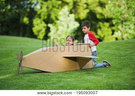Adorable Little Kids Playing With Cardboard Airplane In Green Park